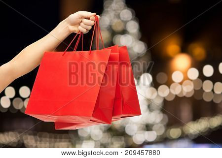 sale, holidays, consumerism and people concept - close up of hand holding red blank shopping bags over christmas tree lights background