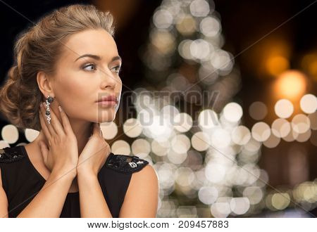 jewelry, holidays, luxury and people concept - beautiful woman in black wearing earrings over christmas tree lights background