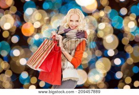 christmas sale and people concept - happy teenage girl or young woman in winter clothes with shopping bags over holidays lights background