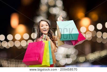 sale, holidays and people concept - smiling woman in red dress with colorful shopping bags over christmas tree lights background