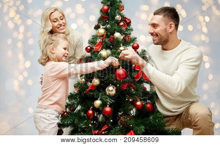 family, holidays and people concept - happy mother, father and little daughter decorating christmas tree over lights background