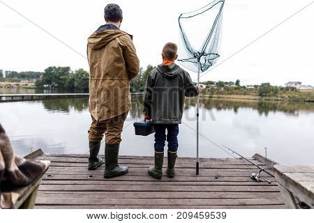 Father And Son Fishing With Rod And Net