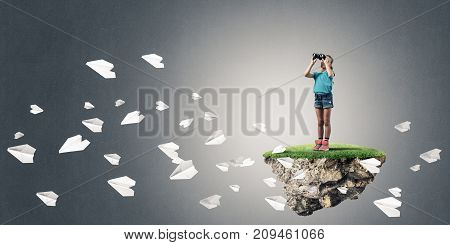 Cute kid girl sitting on floating island against concrete background