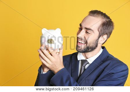 Young man with piggy bank on color background
