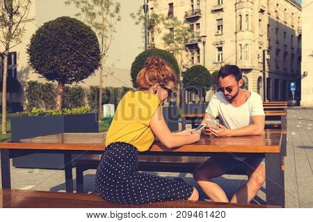 Couple of friends using smart phone outdoors.