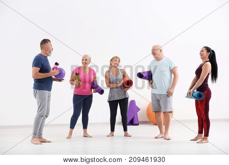Group of mature people with yoga mats indoors