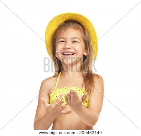 Adorable little girl applying sunscreen onto skin against white background