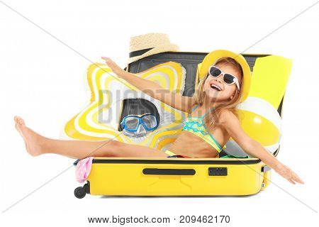 Adorable little girl sitting in suitcase on white background