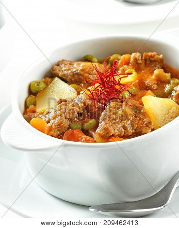 Beef stew in a white cooking pot with potatoes and saffron