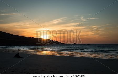 A dusky sunset view of Porthmeor beach at the end of a spring day in the sleepy Cornish fishing village of St. Ives England.