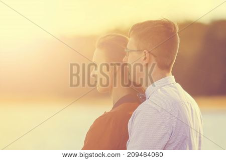 Portrait Of Happy Young Couple In Love On Blurred Background Of Bridge In Autumn. Vintage Tone