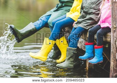 Family Sitting On Wooden Bridge