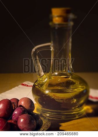 Still life with jar with olive oil and kalamata olives over black background.