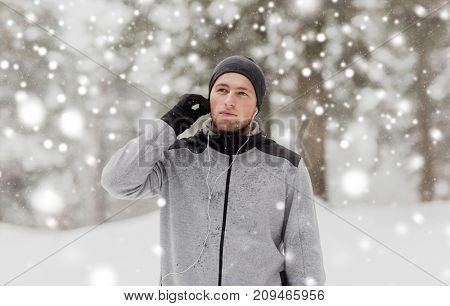fitness, sport, people and healthy lifestyle concept - young man with earphones listening to music in winter forest
