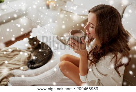 christmas, winter and people concept - happy young woman with cup of coffee or tea in bed at home bedroom over snow