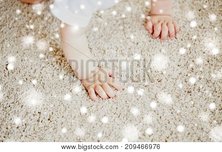 childhood, babyhood and people concept - hands of baby crawling on floor or carpet over snow
