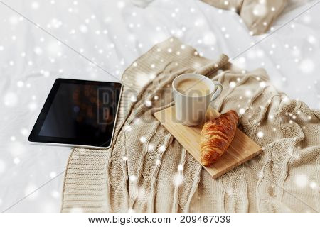 cosy home, morning and winter concept - tablet pc computer, coffee cup and croissant on bed over snow