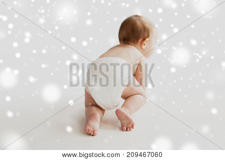 childhood, babyhood and people concept - little baby boy or girl in diaper crawling on white floor over snow