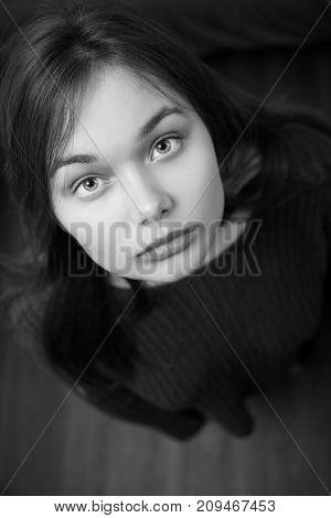 sad beautiful young woman looking up at camera, monochrome