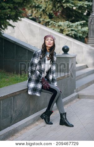 Young beautiful stylish woman, wearing a coat in a white and black cage, white jacket, gray trousers, black boots. Street style, spring and autumn trend, a flirty look.