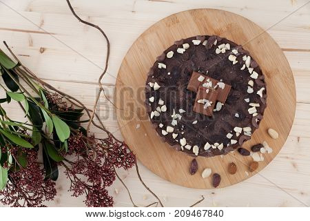 A beautiful plate of raw vegan snickers cake with flowers alongside in a little pastry.