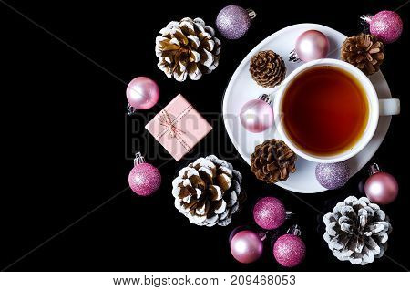 Christmas Balls And A Cup Of Hot Tea Isolated On A Black Background, Top View.