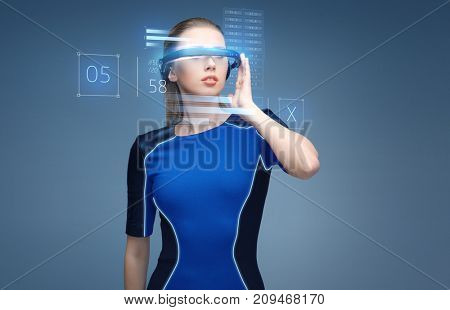 augmented reality, science, technology and people concept - beautiful woman in futuristic 3d glasses with virual charts projection over blue background