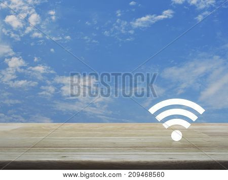 Wi-fi button on wooden table over blue sky with white clouds Technology and internet concept