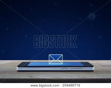 email icon on modern smart phone screen on wooden table over fantasy night sky and moon Business communication concept