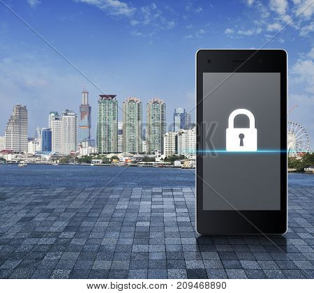 Key icon on modern smart phone screen on stone tile floor over city tower river and blue sky Business internet security concept