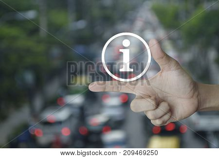 Information sign icon on finger over blur of rush hour with cars and road Business communication concept