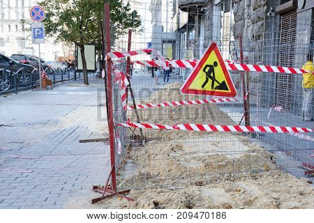 Repair work in the middle of the pedestrian zone in the big city. Sand is poured onto the sidewalk and fenced with a protective tape.