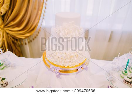 Horizontal view of the white marzipan wedding cake decorated with roses