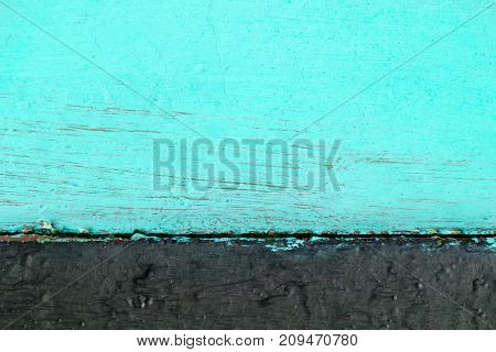 Two-tone wooden background consisting of turquoise color with black.