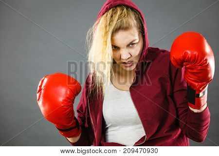 Sporty angry determined woman wearing red boxing gloves fighting and screaming. Studio shot on dark background.