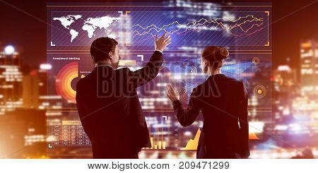Two business people standing with back and working together with virtual screen