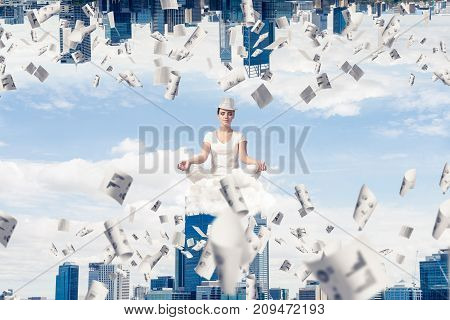 Young woman keeping eyes closed and looking concentrated while meditating on cloud among flying papers and between two urban worlds.