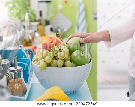 Woman Taking An Apple From A Fruit Bowl