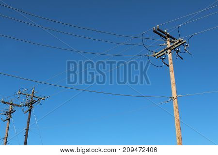 Terminal end of power poles with blue sky behind,