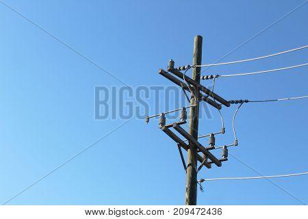 Terminal end of power pole against a deep blue sky,