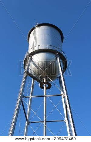 Tall old style water tower against a deep blue sky,