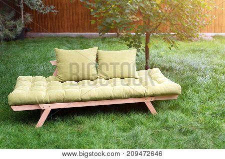 Green sofa in the yard outdoors. Outdoor furniture in green garden patio
