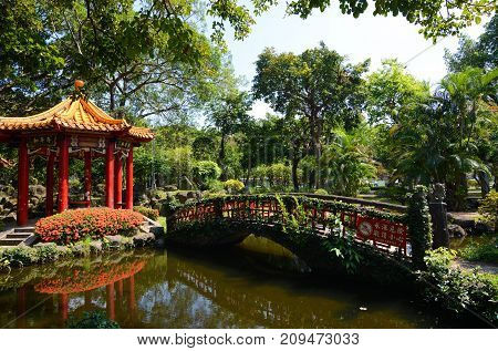 TAIPEI, TAIWAN - August 5, 2017 - Red pagoda reflecting in a small pond at Jieshou Park across from the Presidental Office in Taipei