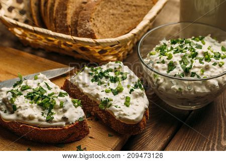 Homemade farm bread with cottage cheese curd and green herb, and curd cream in bowl on wooden table