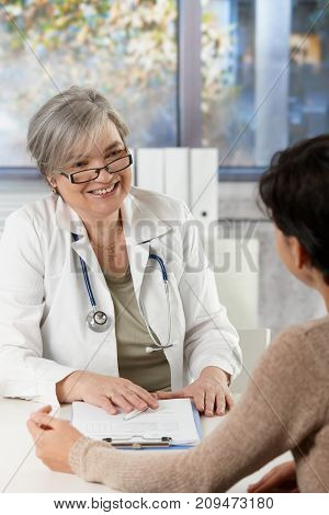Happy mature female doctor sitting at desk in doctor's room talking to patient, smiling.