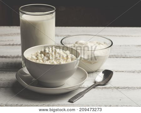 Bowl of white cream, curd and homemade milk on white wooden rustic background, Healthy organic dairy farm food