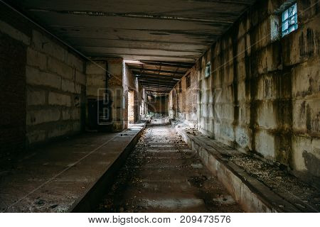 Dark tunnel in old abandoned brick factory. Abandoned industrial corridor, horror creepy mystery building concept, toned