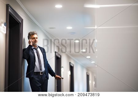 Mature businessman with smartphone in a hotel corridor. Handsome man standing in a hotel corridor, making a phone call.