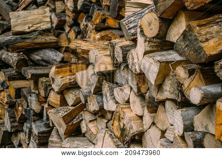 Pile of firewood, dry firewood background, natural wood forest energy concept, selective focus