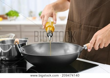Man pouring cooking oil from bottle into frying pan on stove